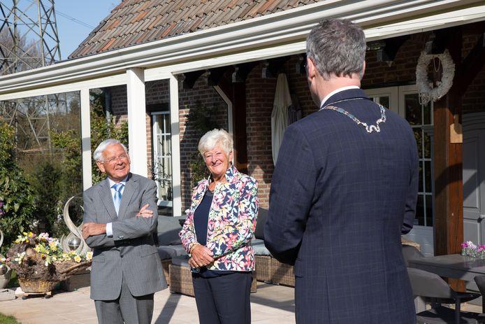 Burgemeester Hans Janssen verrast Piet Gelden in Moergestel met een lintje.