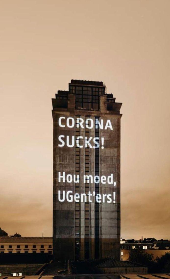 Twee weken lang projecteert de UGent 'corona sucks' op de gevel van de Boekentoren.