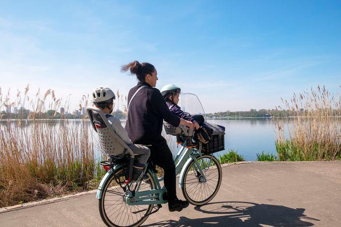 Twee  kinderen in het kinderzitje met een fietshelm op bij de Kralingse Plas.