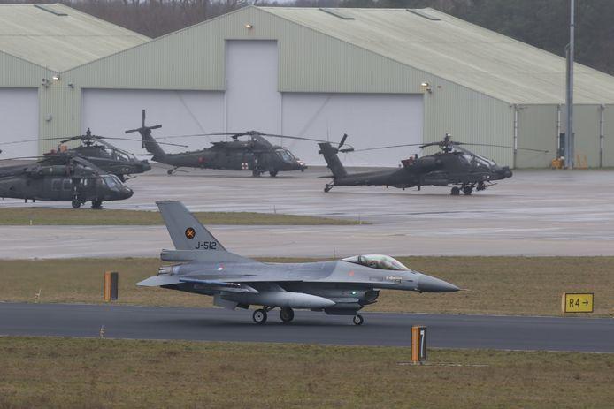 Acht Nederlandse F-16's landden woensdag op de Vliegbasis Eindhoven. Op de achtergrond vier Amerikaanse helikopters, die deze week een tussenstop maken, onderweg naar de thuisbasis.