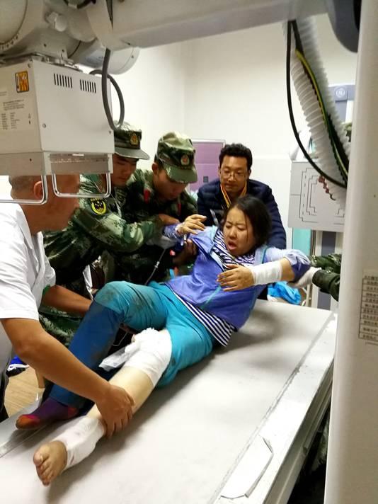 Een gewonde vrouw wordt geholpen.