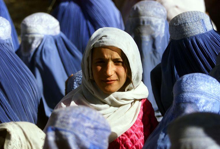 Eind 2001, een Afghaanse vrouw laat voor het eerst in vijf jaar in het openbaar haar gezicht zien; kort ervoor zijn de Taliban door de VS uit Kabul verdreven. Beeld Reuters