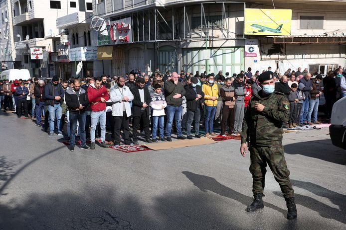 Een Palestijnse soldaat bewaakt mannen die buiten aan een moskee het vrijdagmiddaggebed bidden in de Palestijnse stad Hebron op de Westelijke Jordaanoever.