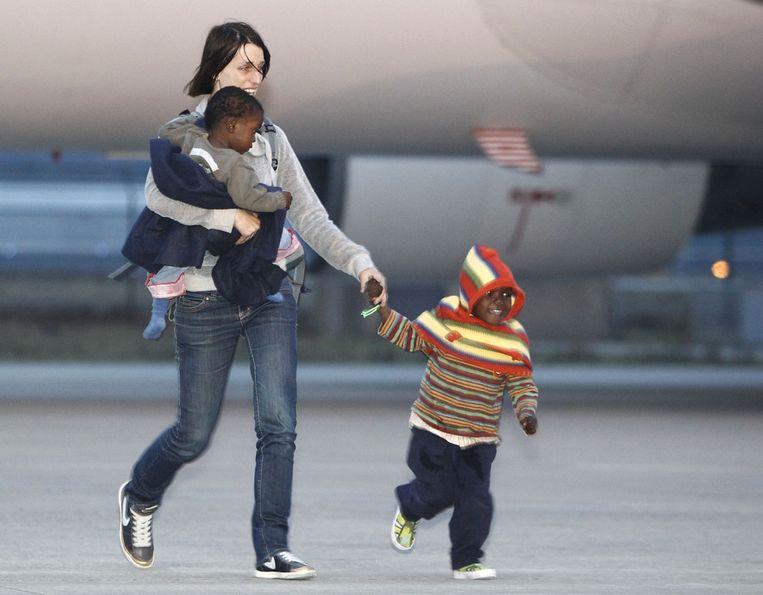 Een moeder op luchthaven Eindhoven met haar adoptiekinderen uit Haïti. Beeld ANP