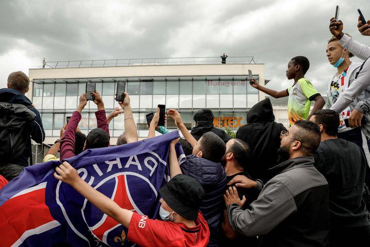 Voor de luchthaven van Le Bourget, bij Parijs, wachten supporters van PSG ongeduldig op de komst van Lionel Messi. Beeld AFP