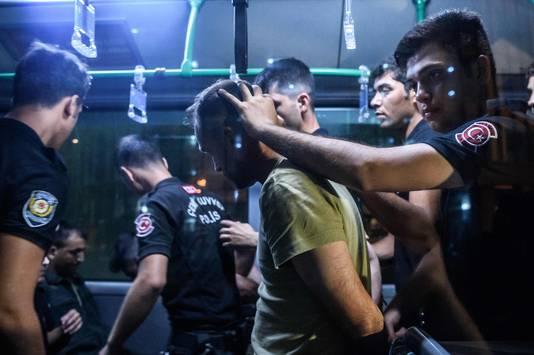 Turkse politieagenten arresteren een militair.