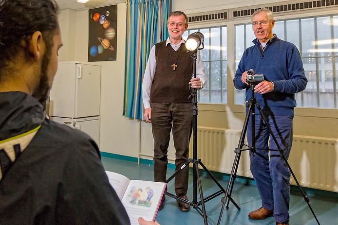 Het video-vader-voorlees-project in de gevangenis van Alphen. Gevangenispastor Jan Lange en vrijwiliger Henri Komen tijdens de opnamen van een verhaal.