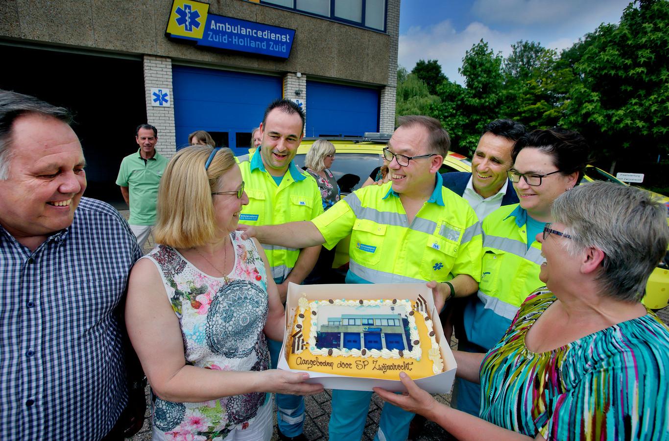 Ria Reijerse (midden), bij de aanbieding van een taart aan Zwijndrechts ambulancepersoneel, als dank voor de inzet. Inmiddels is er niemand meer die zich in de raad voor de partij in wil zetten.