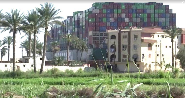 Vanaf een van de oevers een beeld van het gestrande containerschip Ever Given, dat dwars in het Suezkanaal ligt en vastzit tussen de oevers. Beeld Reuters