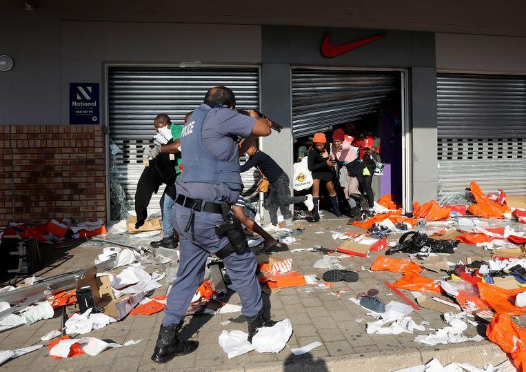 De politie probeert in te grijpen in Durban. Beeld EPA