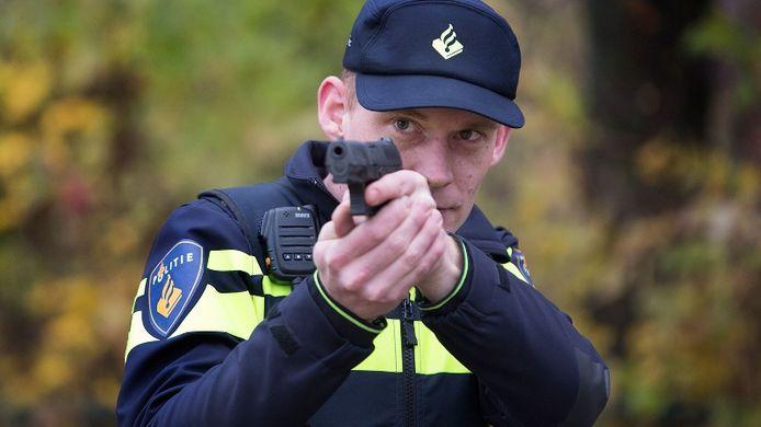 Een agent richt zijn wapen.