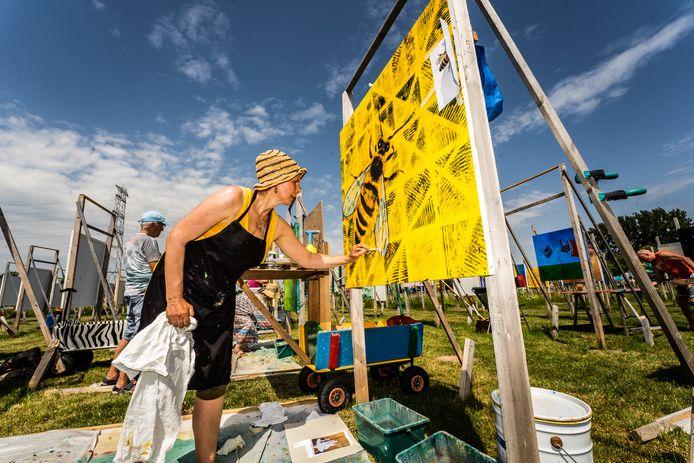 Een van de 450 kunstenaars die meewerkten aan The Colourfield Performance bezig met haar paneel. Het werd aan de buitententoonstelling is nu afgerond.