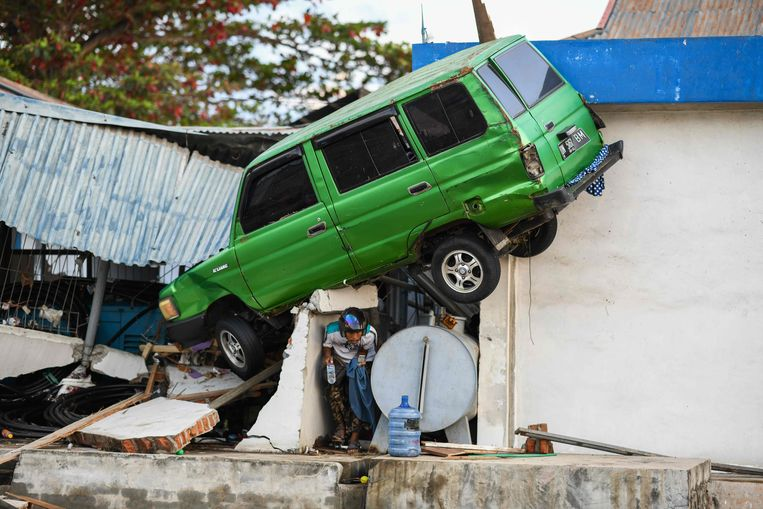 Geen dak meer boven zijn hoofd, wel een door de tsunami meegesleurde auto. Beeld AFP