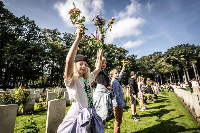 Uitverkoren bloemenkinderen op de Airborne Begraafplaats in Oosterbeek  houden hun bloemen omhoog bij 40 van 1770 graven van gesneuvelden tijdens de Slag om Arnhem.