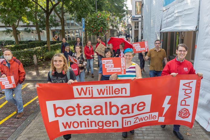 Het Flits-Woonprotest van enkele politieke partijen op weg naar de Thorbeckegracht, waar een groot spandoek hangt met de vraag of Zwolle wel klaar is voor high-end vastgoed. Het antwoord van de PvdA, SP en GroenLinks laat zich raden.