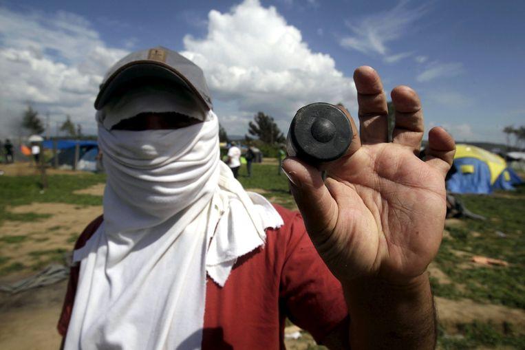 Een migrant laat een rubberkogel zien die zou zijn afgevuurd door de Macedonische veiligheidstroepen. Beeld null