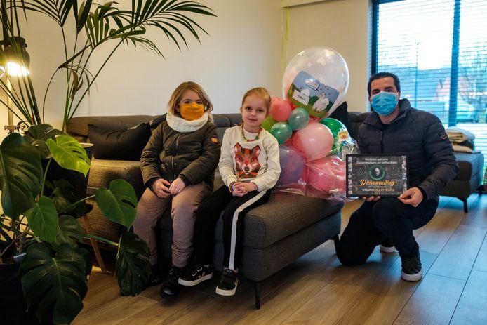 Jurgen Mertens (rechts) en dochter Sienna (links) komen een cheque van 12.980 euro overhandigen aan dorpsgenootje Collette, die lijdt aan een hersenverlamming en epilepsie