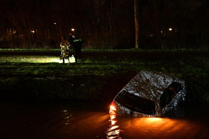De autobestuurder wordt afgevoerd. De auto ligt, met nog brandende lichten, in het water.