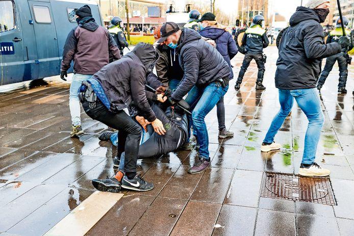 Een van de aanhoudingseenheden aan het werk op het 18 Septemberplein tijdens de rellen van zondag 24 januari. Terwijl een aantal AE'ers een relschopper aanhouden, schermt de rest van het team hun collega's af van de menigte. In deze situatie is ook de ME nog voor het team gaan staan om ze te beveiligen. (Bewerkte versie)