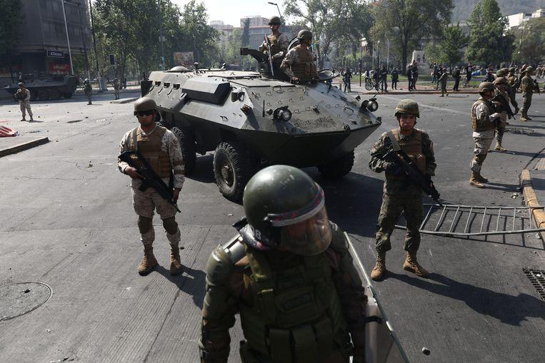 Voor het eerst sinds de militaire dictatuur, die eindigde in 1990, patrouilleerden militairen op straat in de Chileense hoofdstad Santiago. Beeld REUTERS