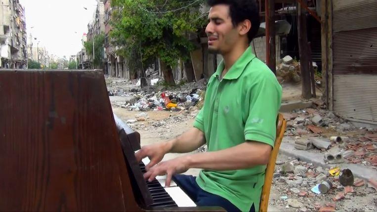 Aeham zingt en speelt een treurlied tussen het oorlogspuin in Yarmouk, een stad in het Syrische gouvernement Damascus.  Beeld rv