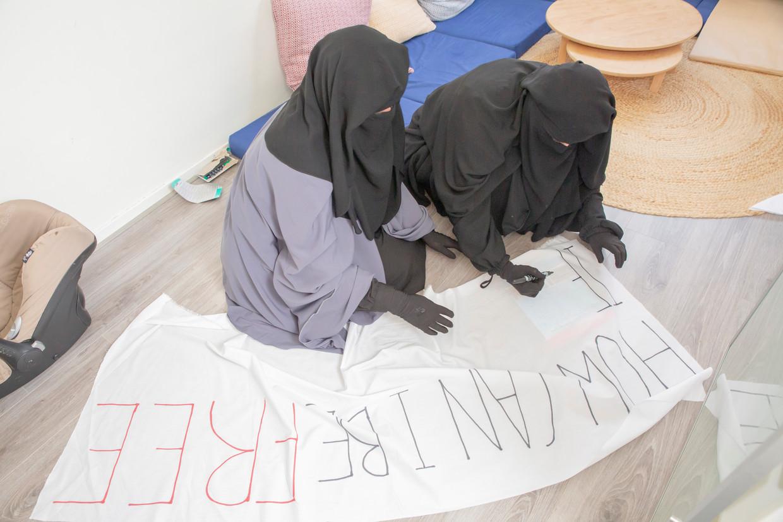 Mouna (in het blauw) en Esther maken spandoeken voor het protest.