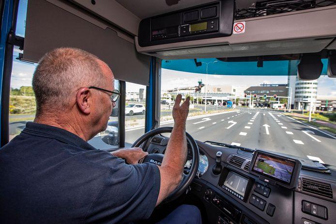 Chauffeur Henk van Steijn in een vrachtwagen met navigatiesysteem waarop de groene golf te zien is.