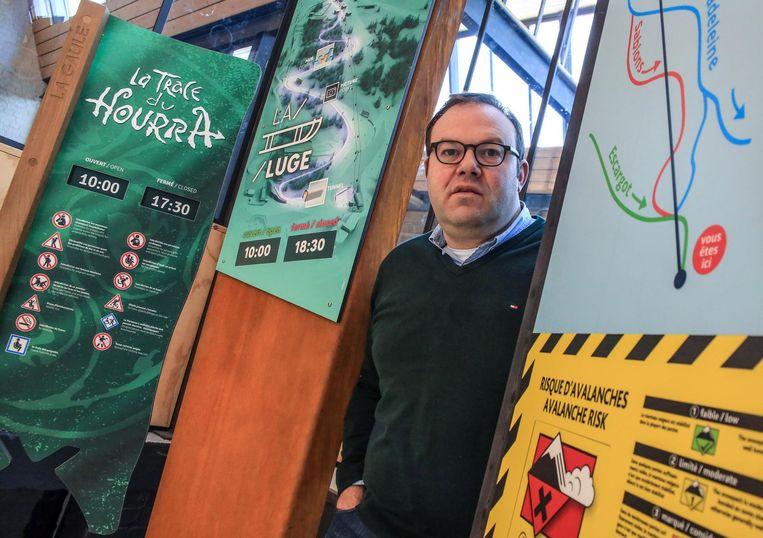 Bedrijfsleider Kristof Flamand met enkele bordjes voor skigebieden.