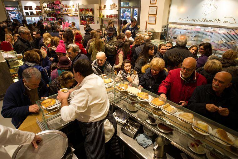 Gezellige drukte in een Madrileense pasteleria, 2016. Spanjaarden zien het als hun verantwoordelijkheid om de bars open te houden en bestellen wat ze kunnen. Beeld Getty Images