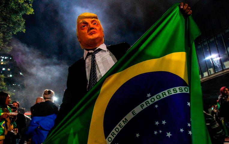 Een supporter van Jair Bolsonaro heeft zich verkleed als Amerikaans president Donald Trump. Beeld AFP
