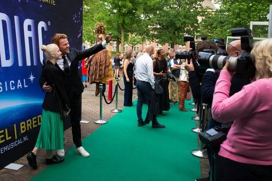 Tijdens de feestelijke première van musical Zodiac passeren tal bekende Nederlanders de groene loper. Zoals Bastiaan Ragas en dochter die voor het oog van de verzamelde paparazzi een selfie nemen