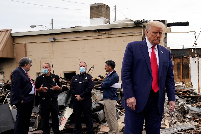 Donald Trump praat met agenten terwijl hij de schade opneemt in Kenosha. Beeld AP