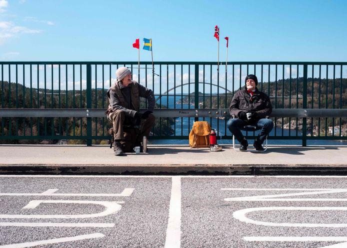 Pontus (links) aan Zweedse zijde en zijn tweelingbroer Ola aan Noorse kant van de grens.