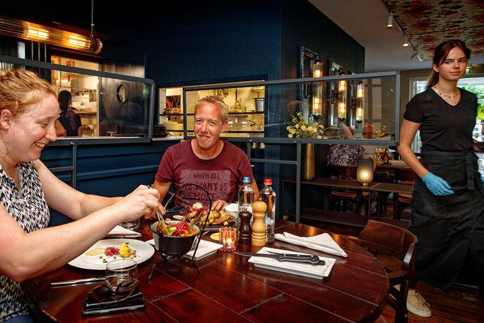 De tafels bij bistro De Heerlijckheid zijn onopvallend afgeschermd met plexiglas.