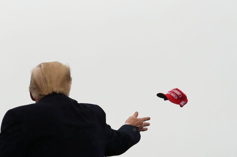 President Trump gooit een 'Make America Great Again'-petje in het publiek tijdens een campagne-evenement in Allentown, Pennsylvania. Beeld REUTERS