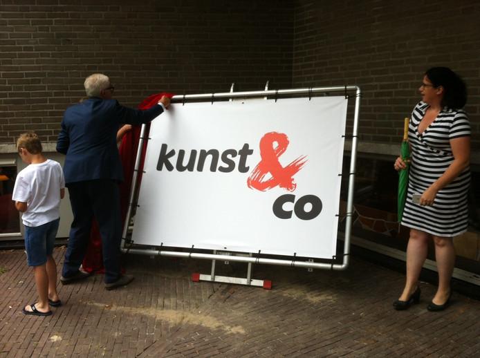 Wethouder Matthie van Merwerode heeft met de kinderen het nieuwe logo van Kunst & Co onthuld. Rechts achter het scherm directeur Janneke van Summeren.