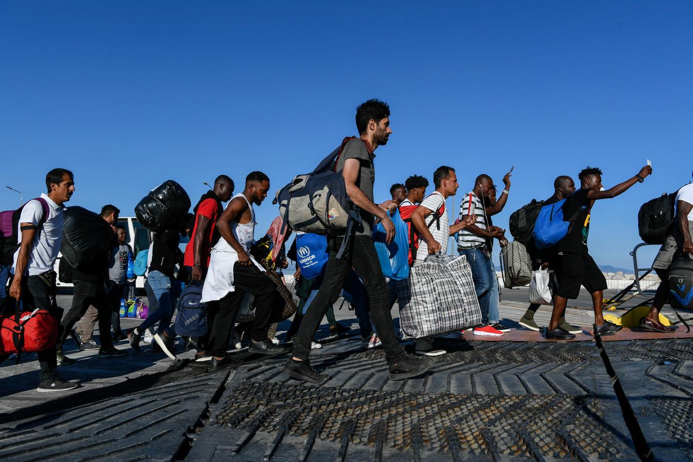 Vluchtelingen en migranten aan een ferry op Lesbos vandaag, op weg naar kampen op het vasteland.
