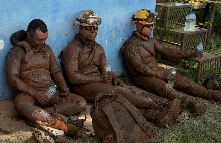 Reddingswerkers die helemaal onder de modder zitten houden even pauze.