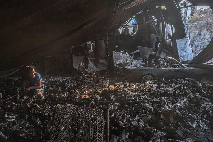 Een Afghaanse jongen zoekt naar eten en drinken in een afgebrande supermarkt in het oude Moria kamp, op Lesbos.