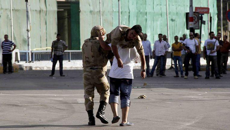 Mannen dragen een gewonde demonstrant in Caïro. Beeld AFP