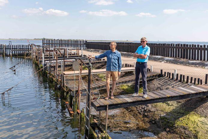 Gijs Niemeijer (links) en Oscar Huiskamp zetten zich in voor het herstelwerk dat nodig is in het haventje van Strijenham.