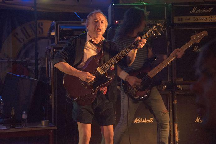 Geheel in de stijl van AC/DC. Headbangen in kostschoolkostuum op keiharde gitaarmuziek.