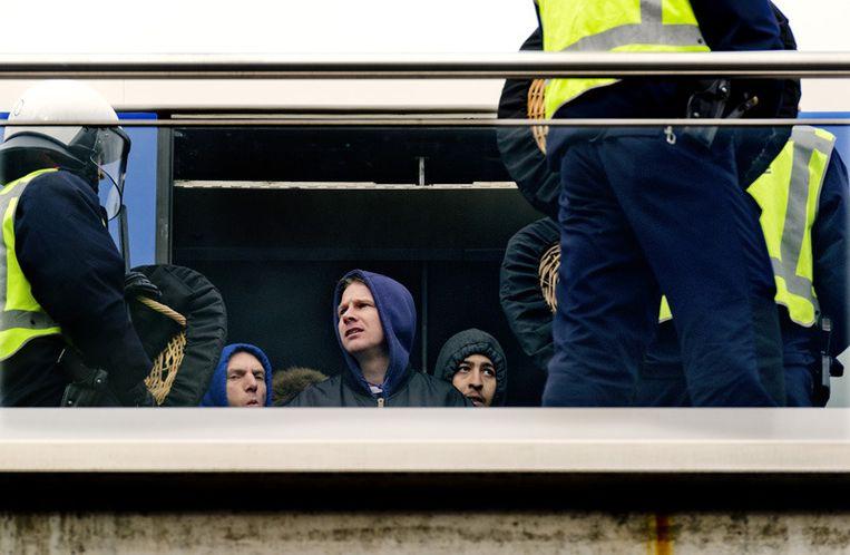 Voetbalhooligans op metrostation Isolatorweg in Amsterdam worden zaterdag een metro in gedreven door de ME. Foto © Koen van Weel/anp Beeld