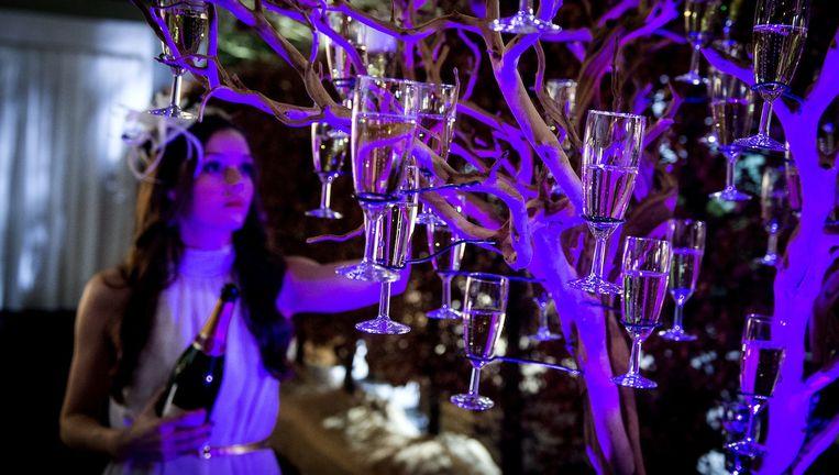 Een dame schenkt een boom vol met glazen champagne voorafgaand aan de opening van de Masters of LXRY. Beeld anp