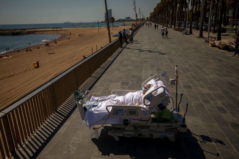 Een herstellende coronapatiënt geniet van het onbelemmerde zicht op het strand van de stad. Beeld AP