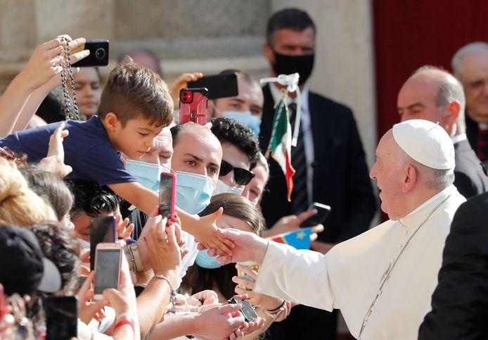 Paus Franciscus raakt de hand van een kind aan.