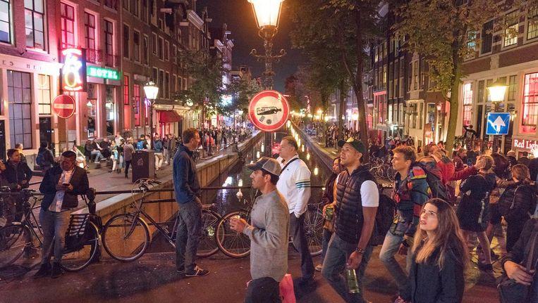 Toeristen op de Wallen negeren het alcoholverbod: het is een pretpark, daar hoort een drankje bij. Beeld Elmer van der Marel