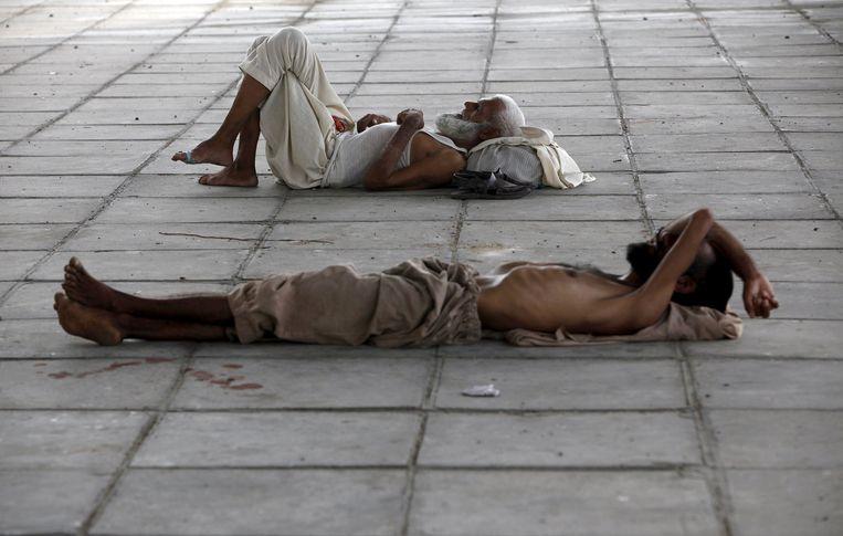 Burgers rusten in de schaduw van een brug in Karachi.