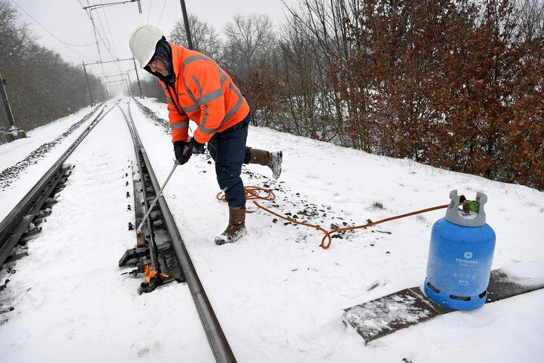 Het treinverkeer ligt stil. Een spoorwegmedewerker probeert een wissel te ontdooien nabij de spoorwegovergang van Ravenstein. Beeld Marcel van den Bergh / de Volkskrant