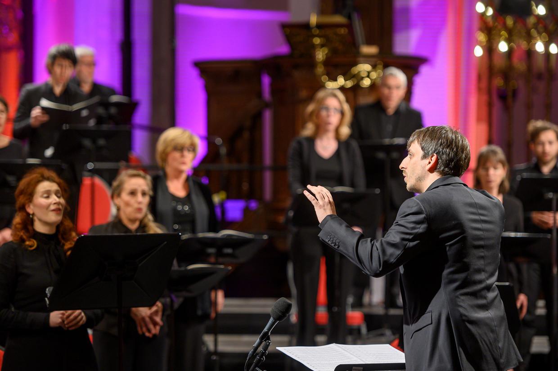 Benjamin Goodson dirigeert het Groot Omroepkoor, vrijdag in de Jacobikerk in Utrecht. Beeld Jelmer de Haas